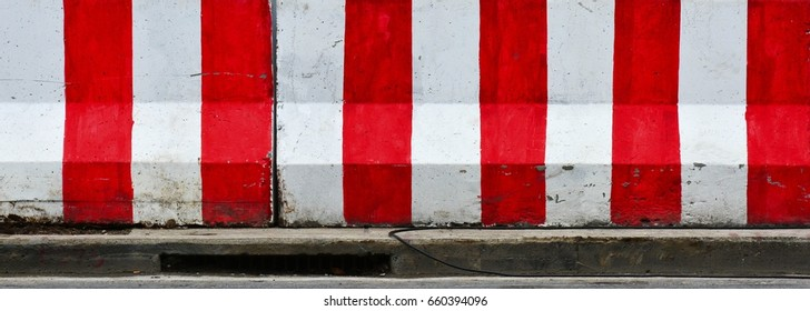 Red and white concrete barriers blocking the road - closeup