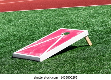 A red and white corn hole game with white chalk on it from the bean bags on a green turf field.