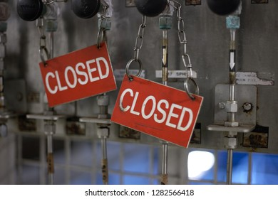 Red and white dirty closed sign. Offshore industry closed sign with steel pipes on background.