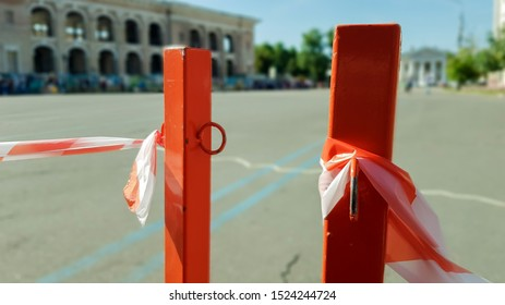Red white does not cross the tape and the metal pole. Signal red and white tape hanging on a metal fence, danger, warning. Ribbon and metal red post. Forbidden tape encloses an unsafe area.