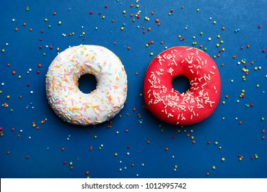 Red and white donuts lie on a blue background. Top view.