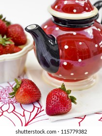 Red and white dotted teapot and a few fresh strawberries over white background