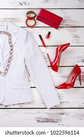 Red and white female outfit. Women white elegant blazer ad red accessories, white wooden background. Feminine fashion background.