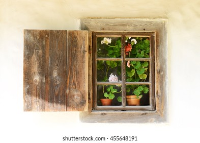 Red and White Flowers of Geranium blooming on the windowsill with old wooden window frame and rustic shutters. Medieval Ukrainian house facade
