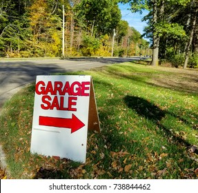 red and white garage sale sign on grass with autumn leaves
