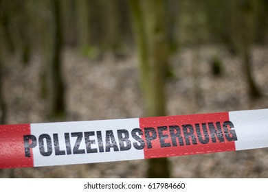 red white german Police Line for Crime Scene Investigation in Forrest in the green