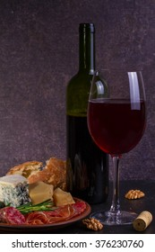 Red and white  glass and bottle of wine. Cheese,  prosciutto, salami, rosemary, nuts, olives and bread on dark rustic wooden background
