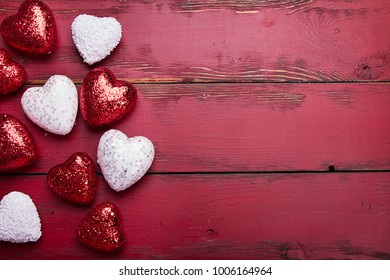 red and white glitter hearts on a red wooden background