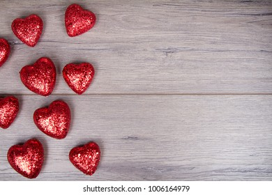 Red and white glitter hearts on wooden background