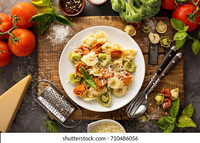Red, white and green cooked tortellini with vegetables and cheese italian food concept overhead shot