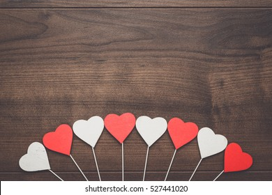 red and white heart shapes on sticks over wooden background