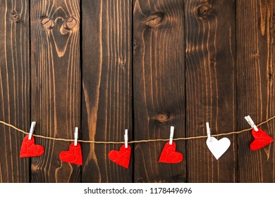 Red and white hearts on a dark wooden background. Background to the day of St. Valentine