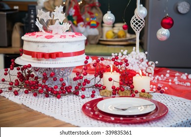 Red and white holiday Christmas table setting with burning candles.