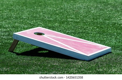 A red and white homemade wooden cornhole board is on a green turf field.