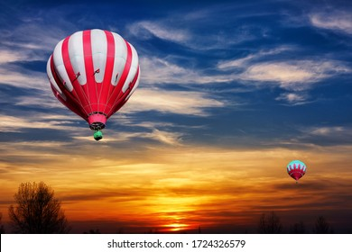 Red and white hot air balloons on the background of bright orange sunset.