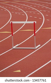 A red and white hurdle in a lane, on a synthetic track