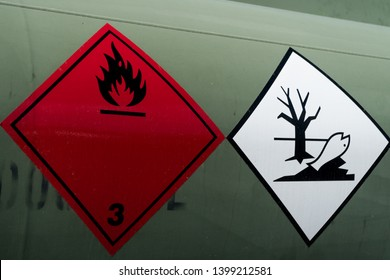 Red and white IMO labels informing about extreme dangerous cargo located on  green crude oil container. Possible pollution.
