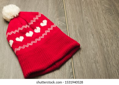 Red and white knitted winter hat with love hearts and bobble