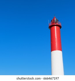 Red and white lighthouse against blue sky
