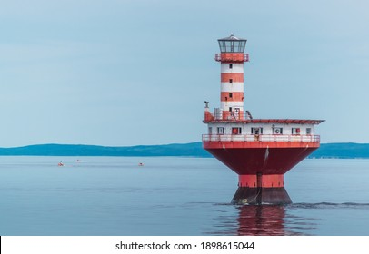 Red and white lighthouse in the middle of the sea in Canada