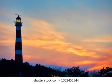 The red and white lighthouse named 'Bornrif', built in the year 1880, near the village of 'Hollum' on the Frisian island 'Ameland', sunset, North Sea, the Netherlands