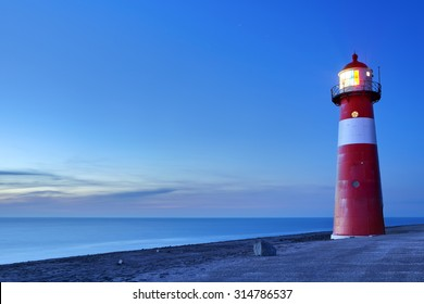A red and white lighthouse at sea. Photographed at dusk near Westkapelle in Zeeland, The Netherlands.