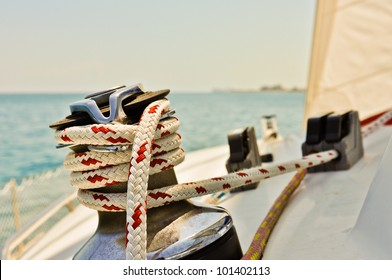 Red and white line wrapped around winch of sailboat