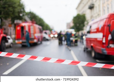 Red and White Lines of barrier tape on the background of firefighters and fire trucks at work.. Red White warning tape pole fencing is protects for No entry.