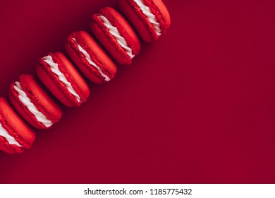 Red and white macarons on red colored background. Copy space for text. Blogger, announcement, ad, banner layout, new year concept