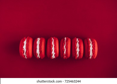 Red and white macarons on red colored background. Minimal food photography concept. Top view, copy space for text.