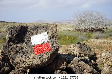 Red and white marks on the rock near trail on the Fuerteventura island, Spain