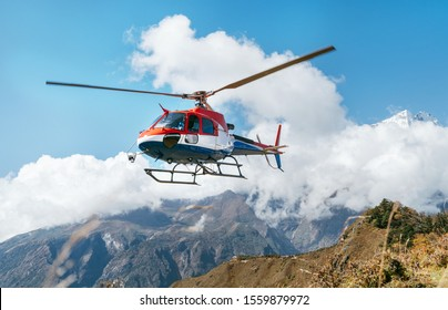 Red and white Medical Rescue helicopter landing in high altitude Himalayas mountains. Safety and travel insurance concept image.