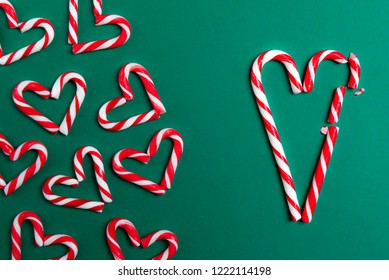 Red and white mini candy canes, arranged in heart shapes, and big candy canes in the shape of a broken heart, on a green background.