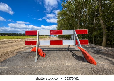 Red and white no entry roadblock on a small asphalt country road