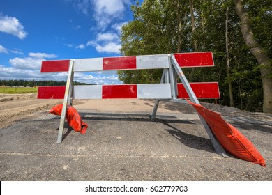 Red and white no entry roadblock on a small asphalt country road and trees in background