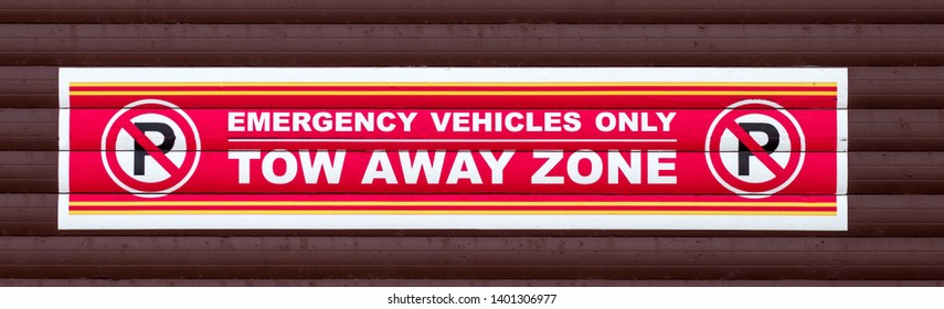 red and white no parking tow away sign for emergency vehicles only on brown background