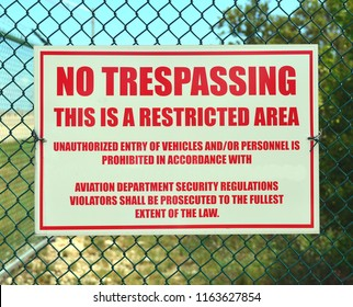 A red and white no trespassing, restricted area sign, mounted on a green fence.