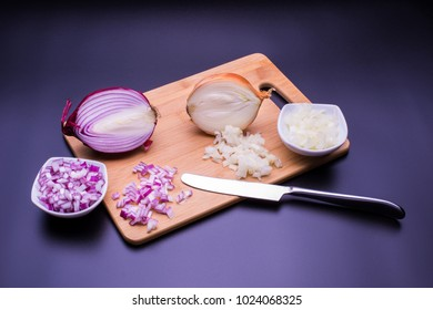 Red and white onion cut and all on a wooden bottom in black background