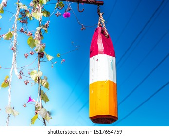 Red, white and orange hanging wooden buoy against a bright blue sky