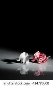 Red and white origami elephants isolated on black background