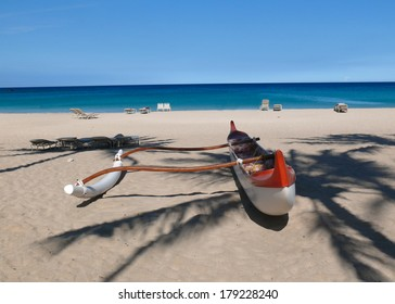 Red and white outrigger at peopleless Kauna'oa Beach, Hawaii
