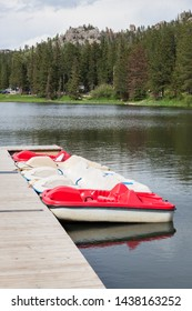 Red and white paddle boats in a row along a dock at Sylvan Lake in South Dakota with a distant shore of trees, vehicles, and granite mountains.