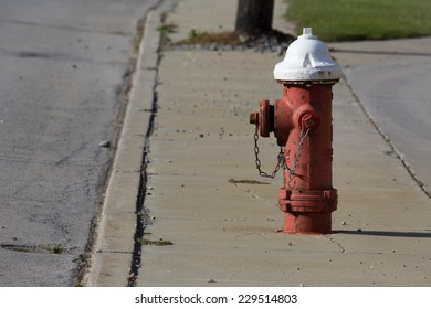 Red and white painted fire hydrant standing watch on a city street.
