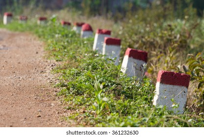 Red and white painted milestones in range on a country road under the sunlight