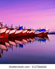 Red and White Phinisi traditional fishery wooden boat at benoa harbour bay bali during sunset