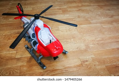 red and white plastic helicopter with  black propeller on wooden floor and background