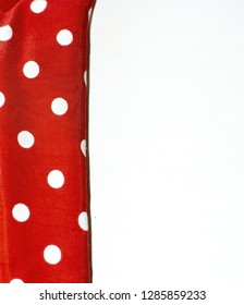 Red and white polka dot fabric margin on white wood background.