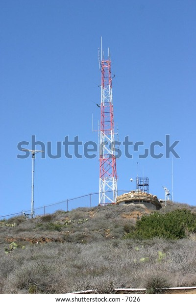 red and white radio tower atop a hill