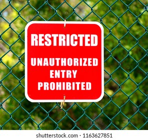 A red and white restricted area, unauthorized entry prohibited sign, mounted on a green fence.