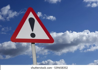 RED AND WHITE ROAD TRAFFIC WARNING SIGN WITH BLACK EXCLAMATION MARK AND BLUE SUMMER SKY